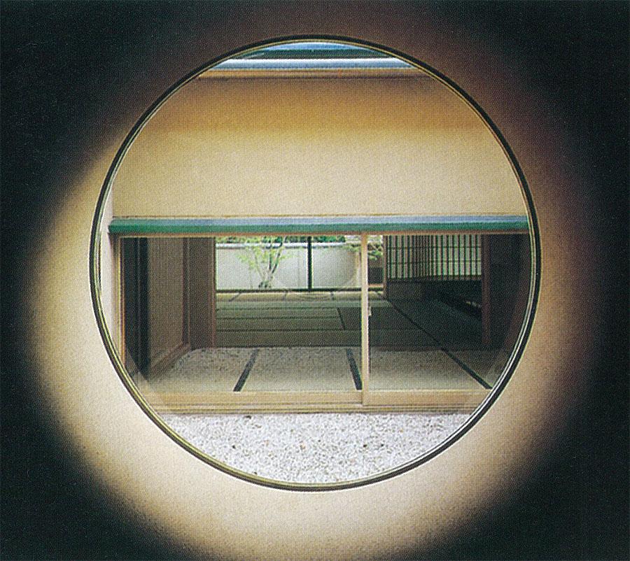 立礼応接室前の廊下に設けられた円窓から玉砂利を敷いた中庭越しに和室を見る