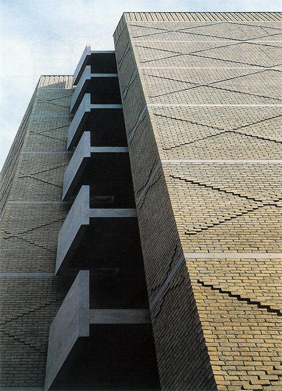 前頁:外部に対してほとんど閉ざされた壁面に3層分の横向きの吹き抜けがある。
